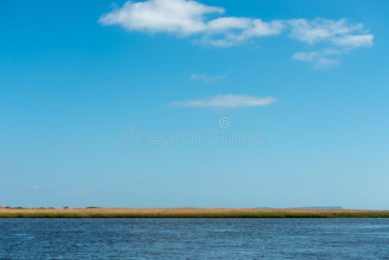 Υπόβαθρο ποταμών και ουρανού με μια λουρίδα της χλόης στοκ φωτογραφίες