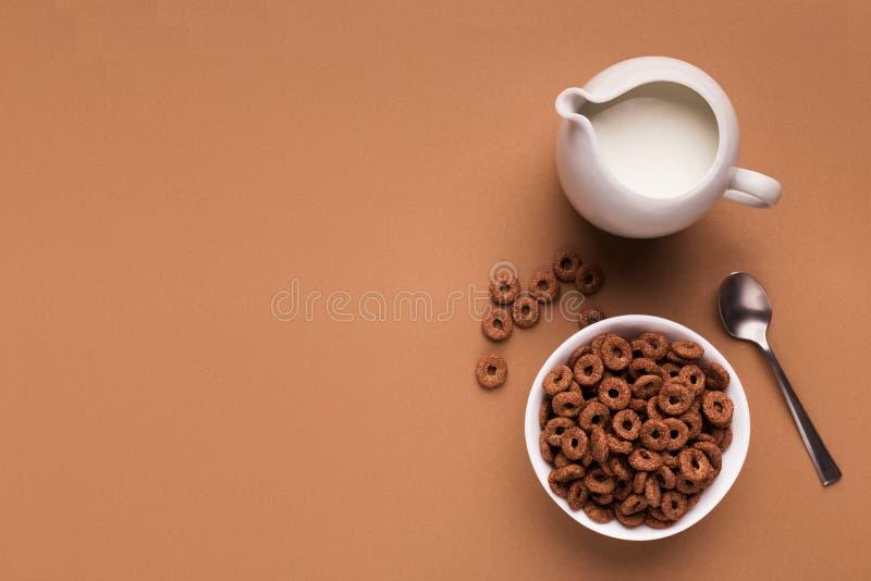Υπόβαθρο προγευμάτων - το γάλα, δημητριακά καλαμποκιού, μετακινεί με το κουτάλι τη τοπ άποψη στοκ φωτογραφία