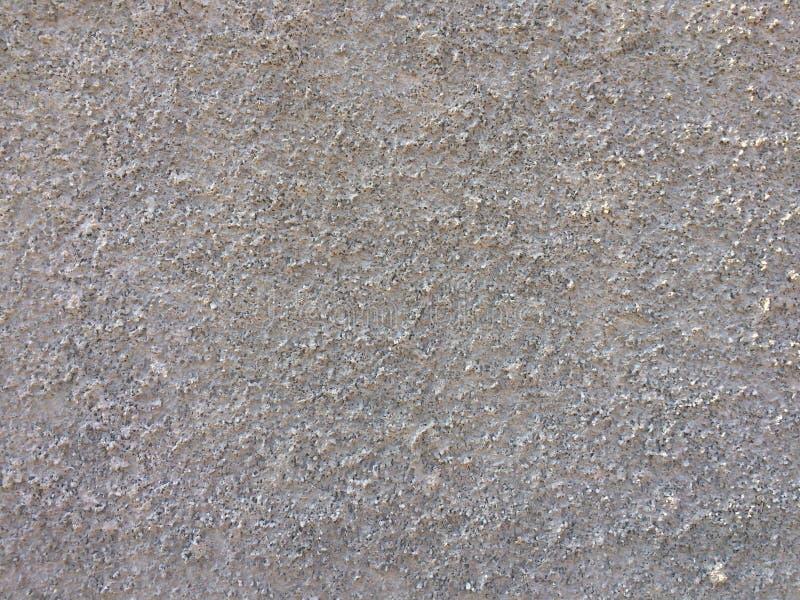 Υπόβαθρο σύστασης ως γκρίζο τοίχο που ψέκασε με τα μικρά μόρια πετρών στοκ φωτογραφίες