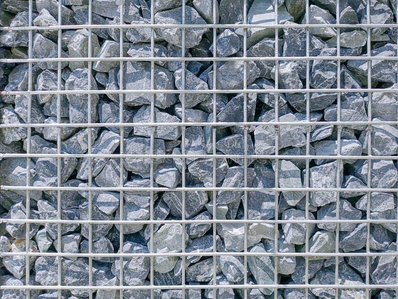 Υπόβαθρο του τοίχου πετρών αμμοχάλικου με το πλέγμα καλωδίων μετάλλων στοκ εικόνα