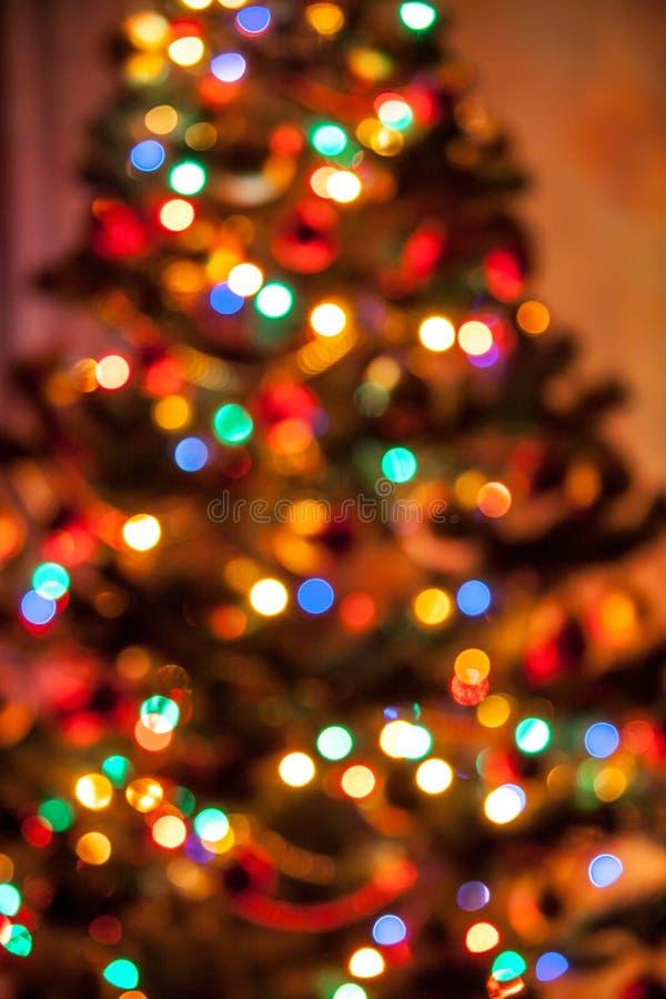 Υπόβαθρο του χριστουγεννιάτικου δέντρου με να λάμψει τα φω'τα στοκ φωτογραφία