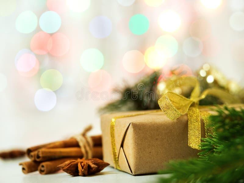 Υπόβαθρο, το δώρο και το έλατο Χριστουγέννων το ελαφρύ διακλαδίζονται, μαγικά να λάμψουν bokeh, κενό διάστημα για το κείμενο στοκ εικόνα