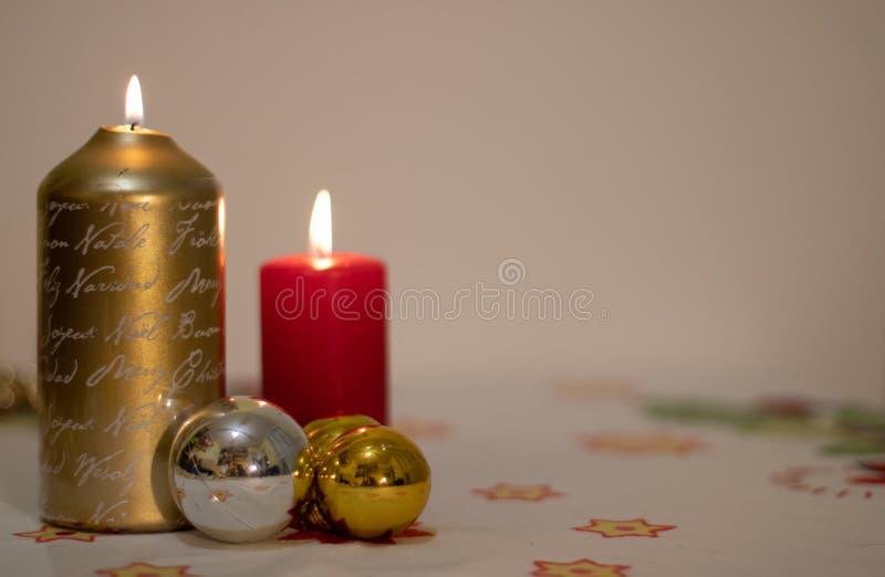 Υπόβαθρο των αναμμένων κεριών με τις σφαίρες Χριστουγέννων σε ένα τραπεζομάντιλο στοκ εικόνες