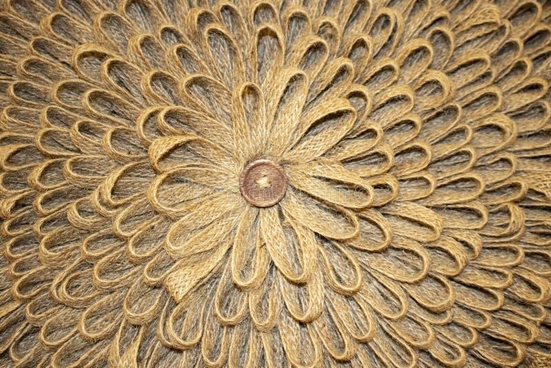 Υπόβαθρο των βρόχων κάνναβης ή burlap στα κυκλικά στρώματα για να κάνει μια αγροτική μορφή λουλουδιών με ένα κουμπί στη μέση στοκ εικόνες