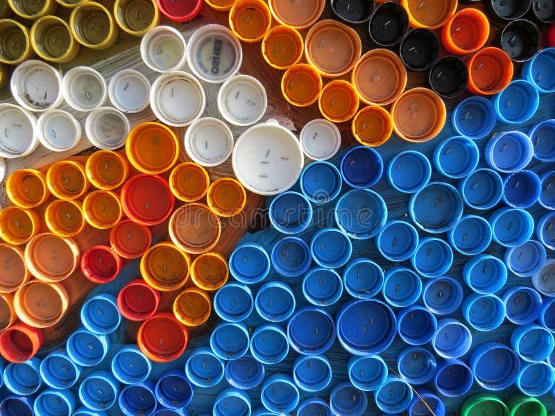 Υπόβαθρο των πλαστικών ζωηρόχρωμων καλυμμάτων μπουκαλιών Μόλυνση με τα πλαστικά απόβλητα Περιβάλλον και οικολογική ισορροπία Τέχν στοκ φωτογραφία