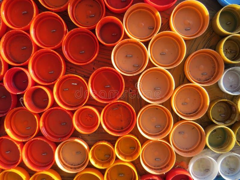 Υπόβαθρο των πλαστικών ζωηρόχρωμων καλυμμάτων μπουκαλιών Μόλυνση με τα πλαστικά απόβλητα Περιβάλλον και οικολογική ισορροπία Τέχν στοκ εικόνες
