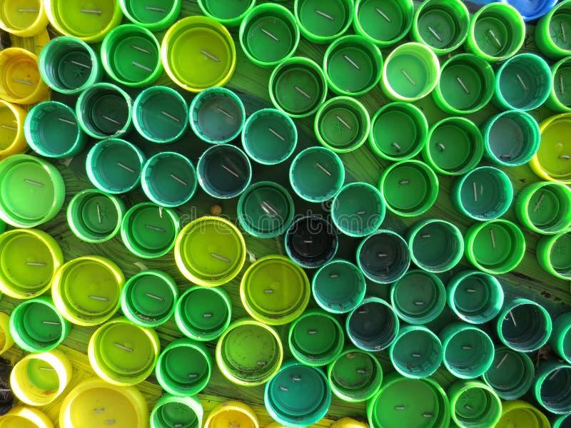 Υπόβαθρο των πλαστικών ζωηρόχρωμων καλυμμάτων μπουκαλιών Μόλυνση με τα πλαστικά απόβλητα Περιβάλλον και οικολογική ισορροπία Τέχν στοκ φωτογραφίες