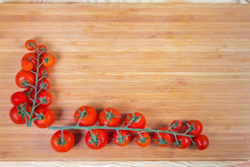 Υπόβαθρο των συστάδων ντοματών κερασιών στον τέμνοντα πίνακα μπαμπού στοκ εικόνα
