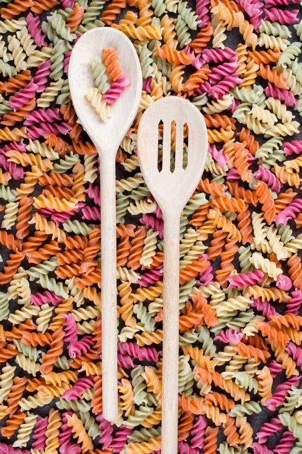 Υπόβαθρο των φωτεινών ζωηρόχρωμων ξηρών ζυμαρικών που γίνεται από τα λαχανικά στοκ φωτογραφία