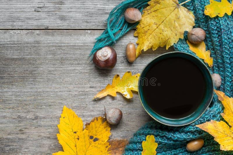 Υπόβαθρο φθινοπώρου με τα ξηρά φύλλα, το μαντίλι και το καυτό φλιτζάνι του καφέ στον ξύλινο πίνακα στοκ εικόνα