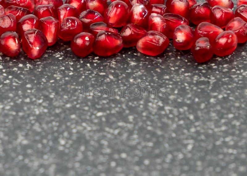 Υπόβαθρο φιαγμένο από κόκκινους σπόρους ροδιών Τα διεσπαρμένα κόκκινα σιτάρια ενός ροδιού στοκ φωτογραφία