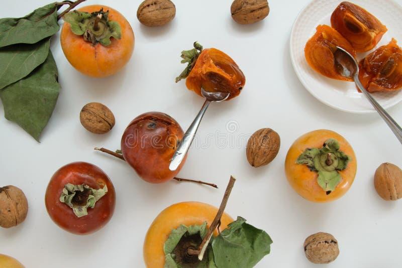 Υπόβαθρο φρούτων φθινοπώρου - ακατέργαστα persimmons και καρύδια στο άσπρο υπόβαθρο στοκ φωτογραφίες