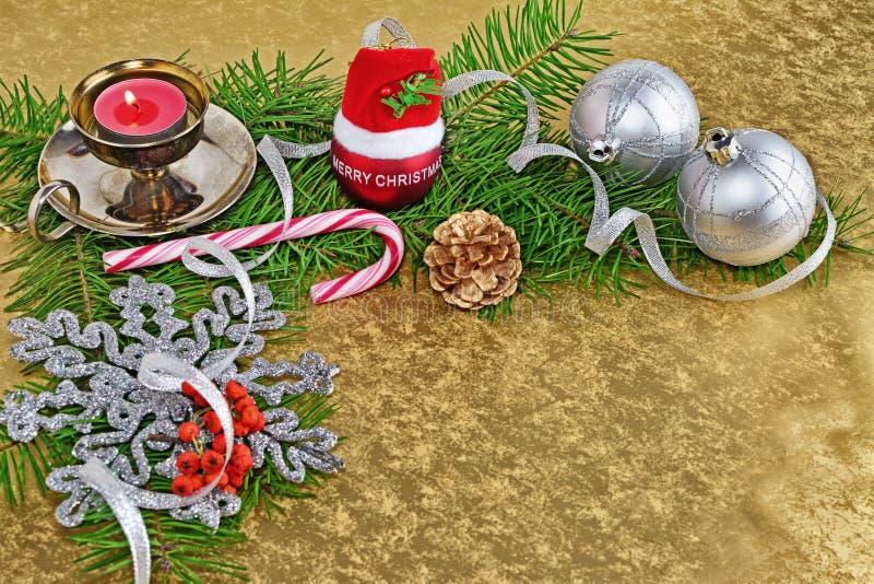 Υπόβαθρο Χριστουγέννων, κάρτα με τα μπιχλιμπίδια, δώρο, έλατο και διακοσμήσεις πέρα από το χρυσό υπόβαθρο στοκ εικόνα με δικαίωμα ελεύθερης χρήσης
