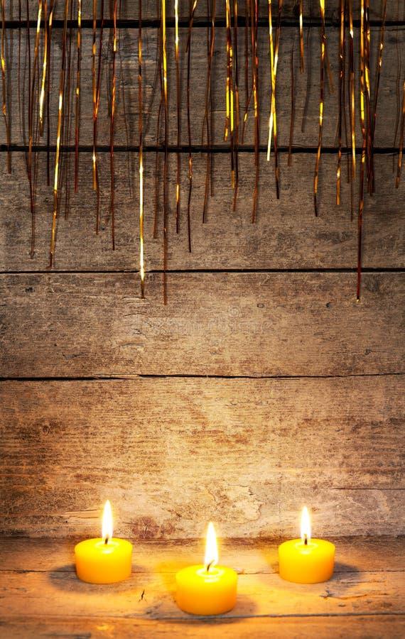 Υπόβαθρο Χριστουγέννων με τα κεριά και tinsel στοκ εικόνες