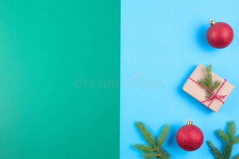 Υπόβαθρο Χριστουγέννων με τον κλάδο δέντρων έλατου, τη σφαίρα Χριστουγέννων και το κιβώτιο δώρων στο μπλε και πράσινο υπόβαθρο στοκ εικόνες