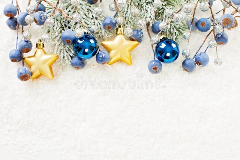 Υπόβαθρο Χριστουγέννων με τον κλαδίσκο χριστουγεννιάτικων δέντρων, τα χρυσά αστέρια, τις μπλε σφαίρες γυαλιού και τα μούρα στο άσ στοκ εικόνα με δικαίωμα ελεύθερης χρήσης