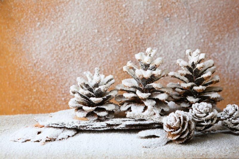 Υπόβαθρο Χριστουγέννων με τους κώνους πεύκων, διακοσμήσεις στοκ εικόνα