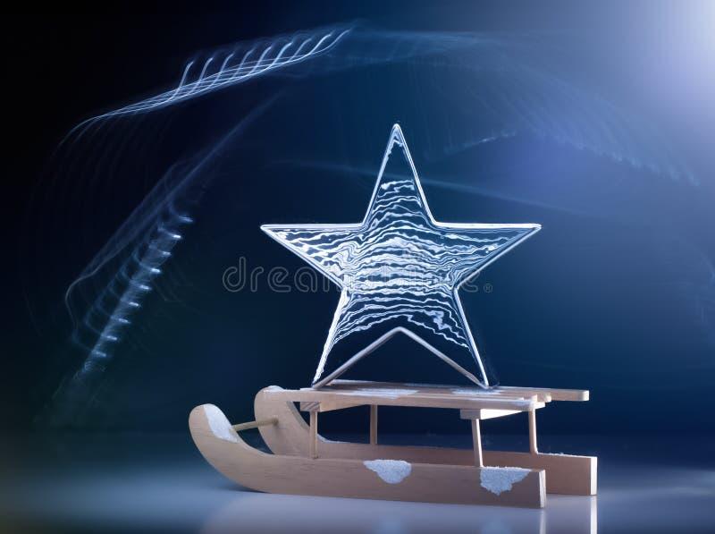 Υπόβαθρο Χριστουγέννων με το έλκηθρο, το μεγάλο ασημένιο μεταλλικό αστέρι και τα Χριστούγεννα ελαφριών αποτελεσμάτων απεικόνιση αποθεμάτων