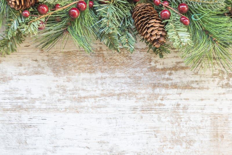 Υπόβαθρο Χριστουγέννων με το δέντρο έλατου, το κόκκινες μούρο και τη διακόσμηση στο λευκό ξύλινο πίνακα Τοπ άποψη με το διάστημα  στοκ εικόνες