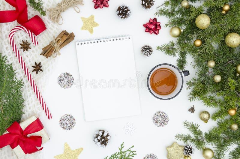 Υπόβαθρο Χριστουγέννων με το κενό σπειροειδές σημειωματάριο, τους κλάδους και τους κώνους έλατου, τις διακοσμήσεις Χριστουγέννων, στοκ εικόνα