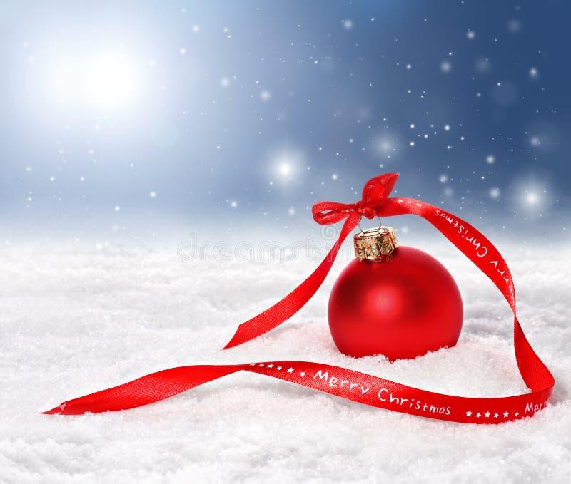 Υπόβαθρο Χριστουγέννων με το κόκκινες μπιχλιμπίδι και την κορδέλλα Χαρούμενα Χριστούγεννας στοκ εικόνες με δικαίωμα ελεύθερης χρήσης