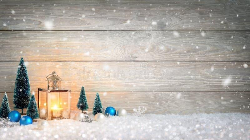 Υπόβαθρο Χριστουγέννων με το ξύλο, το χιόνι και το φανάρι στοκ εικόνες