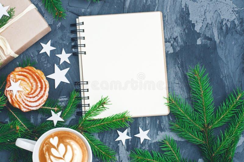Υπόβαθρο Χριστουγέννων με το σημειωματάριο και το cuo του cappuccino στοκ εικόνα