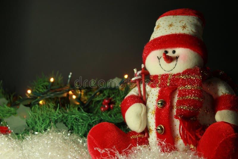 Υπόβαθρο Χριστουγέννων με το χιονάνθρωπο και φω'τα στο στεφάνι πεύκων, sui στοκ φωτογραφίες