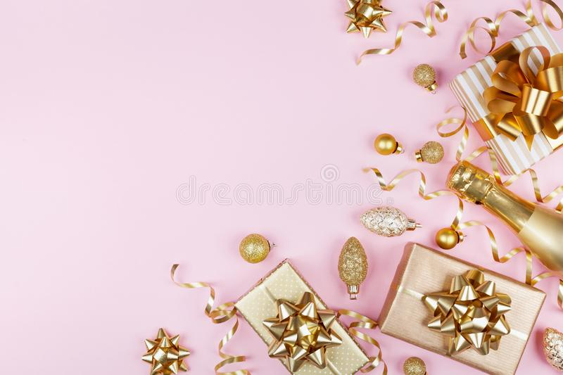 Υπόβαθρο Χριστουγέννων με το χρυσό δώρο ή παρούσες διακοσμήσεις κιβωτίων, σαμπάνιας και διακοπών στη ρόδινη άποψη επιτραπέζιων κο στοκ φωτογραφία με δικαίωμα ελεύθερης χρήσης