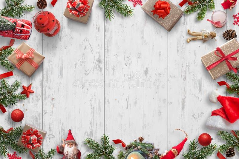 Υπόβαθρο Χριστουγέννων στο άσπρο ξύλινο γραφείο με το χριστουγεννιάτικο δέντρο, δώρα, κούκλες, σφαίρες, καπέλο Santa, κεριά, φανά στοκ εικόνα