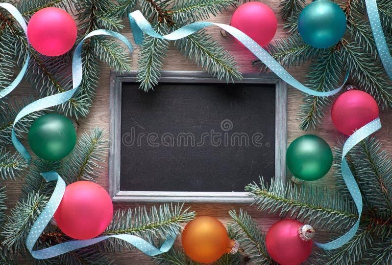 Υπόβαθρο Χριστουγέννων στο ξύλο με τον πίνακα, κλαδίσκοι έλατου, colorfu στοκ εικόνες με δικαίωμα ελεύθερης χρήσης
