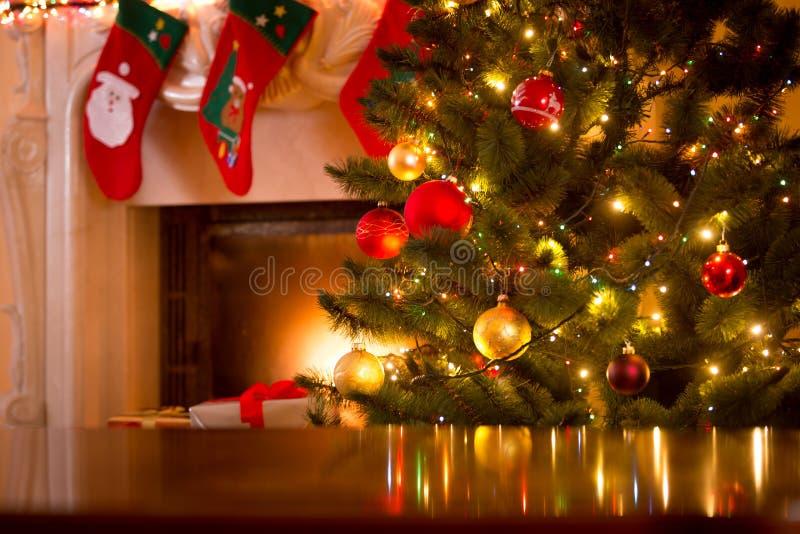 Υπόβαθρο Χριστουγέννων του πίνακα ενάντια στο χριστουγεννιάτικο δέντρο και το firepla στοκ φωτογραφία με δικαίωμα ελεύθερης χρήσης