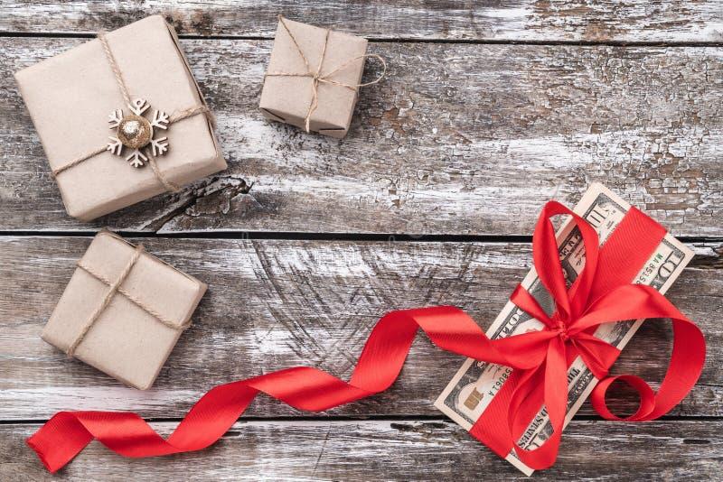 Υπόβαθρο Χριστουγέννων του παλαιού ξύλου, των χρημάτων που εξωραΐζονται με την κόκκινη βραδύτητα και των δώρων Τοπ όψη στοκ φωτογραφία