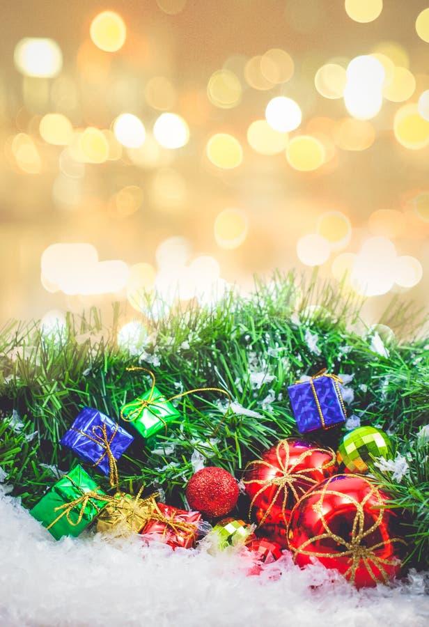 Υπόβαθρο Χριστουγέννων το δώρο που εγκιβωτίζεται με και σφαίρες στο χιόνι στοκ εικόνες
