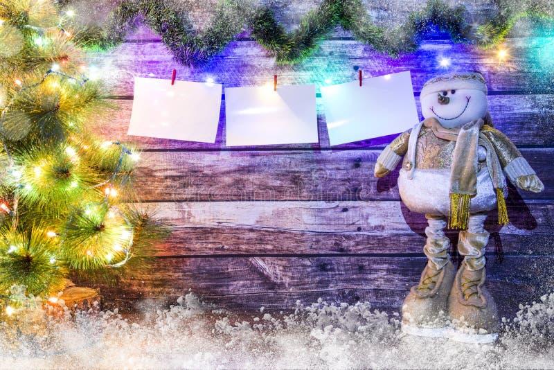 Υπόβαθρο Χριστουγέννων των σκοτεινών ξύλινων πινάκων, fir-tree, του χιονανθρώπου και της φωτεινής γιρλάντας με τα χρωματισμένα φω στοκ εικόνα με δικαίωμα ελεύθερης χρήσης