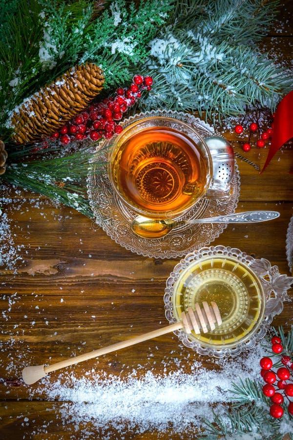 Υπόβαθρο Χριστουγέννων, φλυτζάνι του τσαγιού με το μέλι και croissant, κλάδος ενός χριστουγεννιάτικου δέντρου στο χιόνι στοκ φωτογραφία
