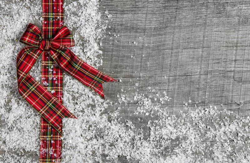 Υπόβαθρο Χριστουγέννων ύφους χώρας με την κόκκινη πράσινη ελεγχμένη κορδέλλα στοκ φωτογραφία με δικαίωμα ελεύθερης χρήσης