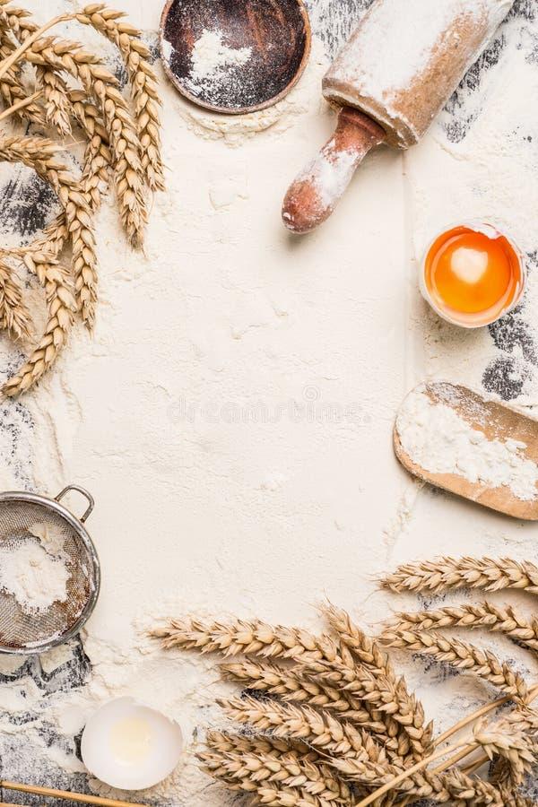 Υπόβαθρο ψησίματος αλευριού με το ακατέργαστο αυγό, την κυλώντας καρφίτσα και το αυτί σίτου στοκ φωτογραφία με δικαίωμα ελεύθερης χρήσης