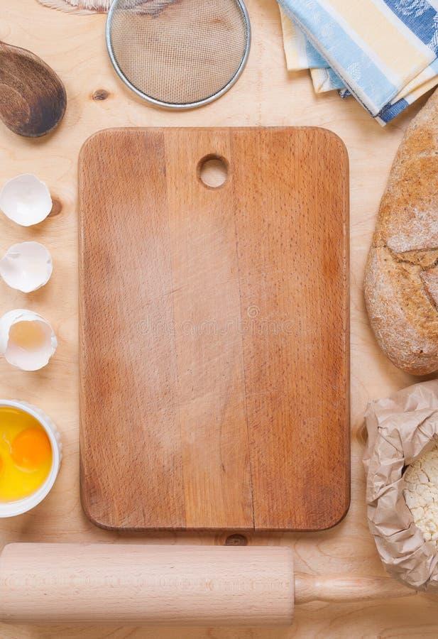 Υπόβαθρο ψησίματος με τον τέμνοντα πίνακα, eggshell, αλεύρι, κύλισμα π στοκ εικόνα με δικαίωμα ελεύθερης χρήσης