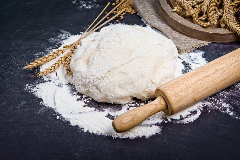 Υπόβαθρο ψησίματος με το αλεύρι, την κυλώντας καρφίτσα και τα αυτιά σιταριού στο blac στοκ εικόνες