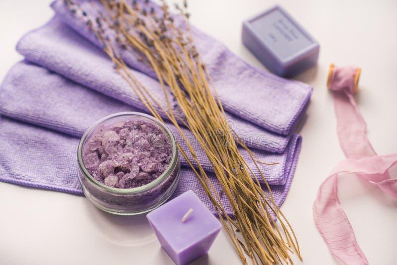 Υπόβαθρο SPA, κερί σε ένα πιατάκι με τα αλατισμένα λουτρά και τα κλαδάκια lavender στοκ φωτογραφία με δικαίωμα ελεύθερης χρήσης