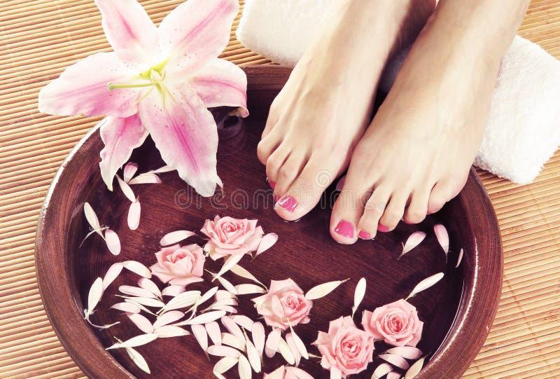 Υπόβαθρο SPA με τα όμορφα πόδια, τα λουλούδια και τα πέταλα στοκ φωτογραφίες