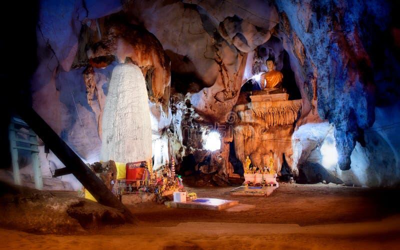Υπόγεια σπηλιά στην Ασία με τους γιγαντιαίους σταλαγμίτες, τους σταλακτίτες και το γιγαντιαίο άγαλμα του Βούδα στο κέντρο της αίθ στοκ φωτογραφία