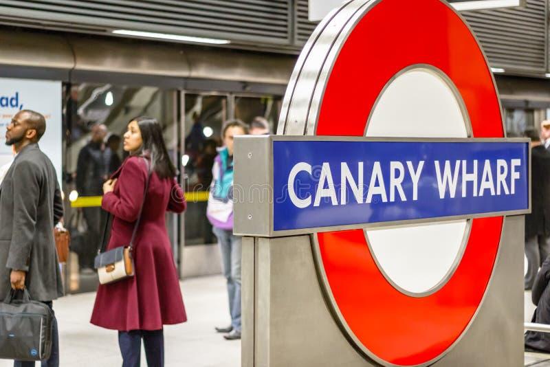 Υπόγειο σημάδι Canary Wharf με τους κατόχους διαρκούς εισιτήριου που περιμένουν σε ένα platfo στοκ εικόνες