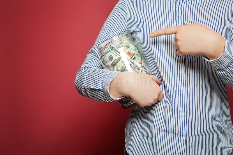 Υπόδειξη των αμερικανικών δολαρίων χεριών και χρημάτων στο βάζο στο ρόδινο υπόβαθρο στοκ εικόνες
