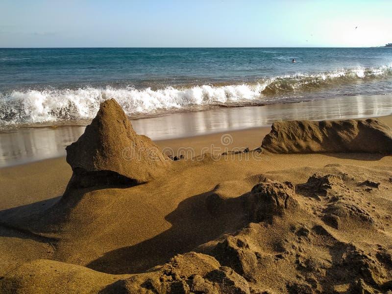 υπόλοιπα ενός κάστρου άμμου στην ακτή μιας παραλίας που καταστράφηκε ακριβώς από τα κύματα της μπλε θάλασσας : στοκ εικόνες