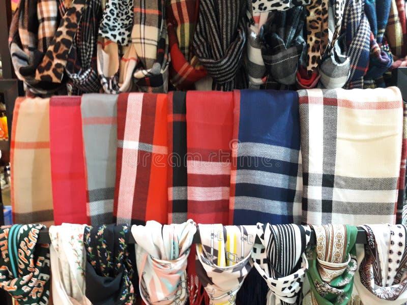 Υπόλοιπος κόσμος ενός όμορφου χρωματισμένου woman' τα μαντίλι του s έδεσαν τον κόμβο στο ράφι που κρεμά στο κατάστημα, ποικιλ στοκ φωτογραφία με δικαίωμα ελεύθερης χρήσης