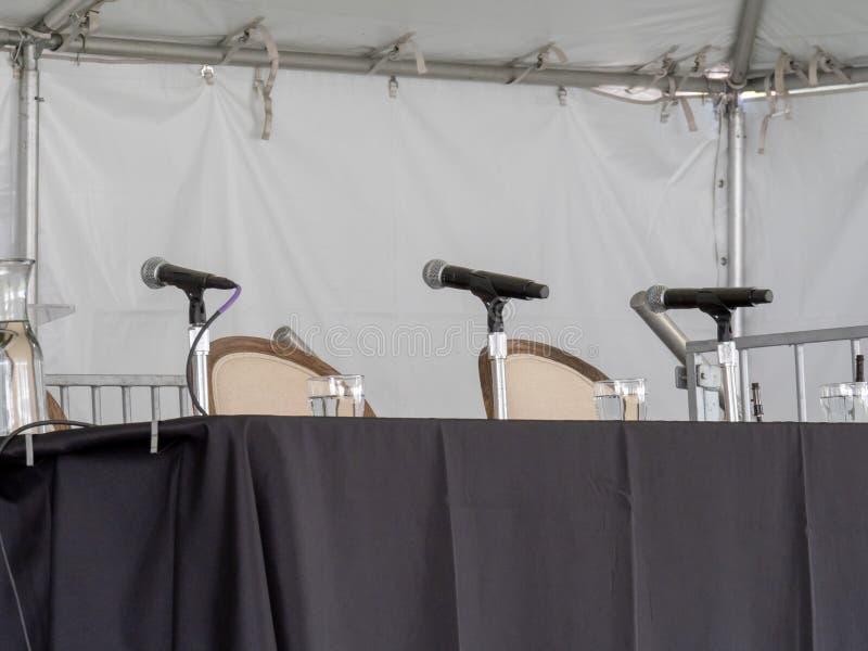 Υπόλοιπος κόσμος των μικροφώνων που κάθονται στον πίνακα, που αναμένει τους ομιλητές στοκ φωτογραφία με δικαίωμα ελεύθερης χρήσης