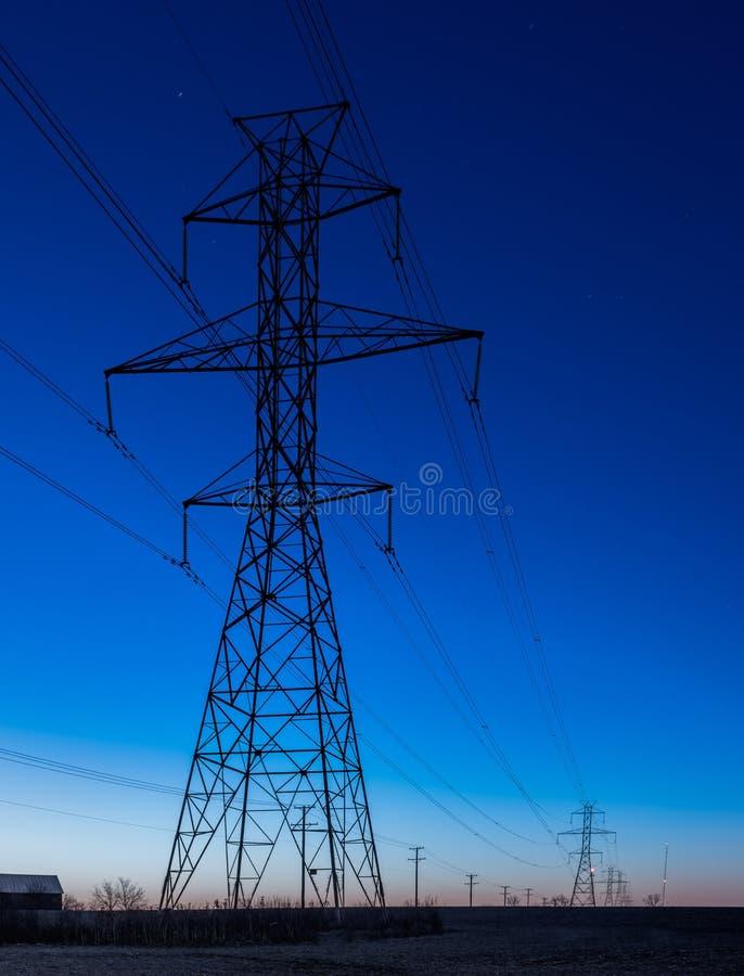 Υπόλοιπος κόσμος των πύργων ηλεκτροφόρων καλωδίων κατά τη διάρκεια της μπλε ώρας στοκ εικόνα