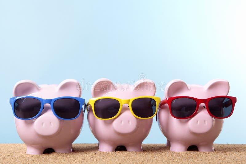 Υπόλοιπος κόσμος τριών piggy τραπεζών, χρήματα ταξιδιού, έννοια αποταμίευσης διακοπών παραλιών, διάστημα αντιγράφων στοκ εικόνες